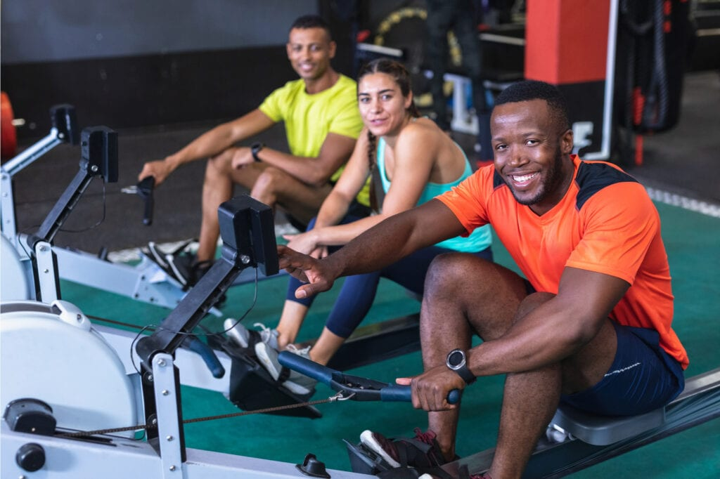 two men and a woman sitting on rowing machines and smiling