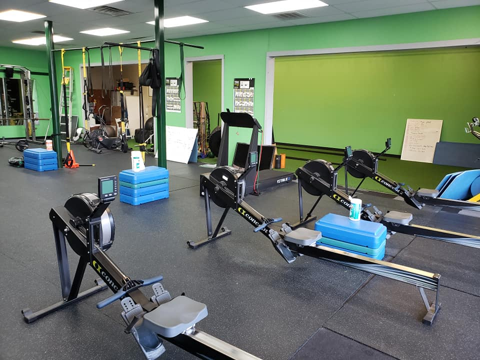 rowing machines, TRX, step blocks, and a treadmill in a small open exercise room