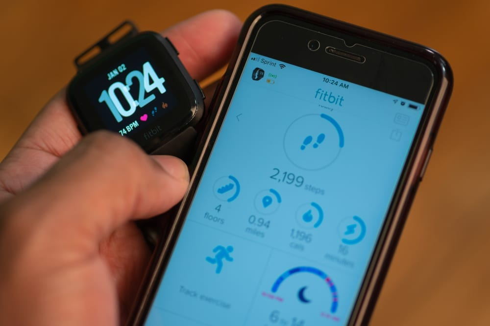 Hand holding fitbit watch next to phone with FitBit app open