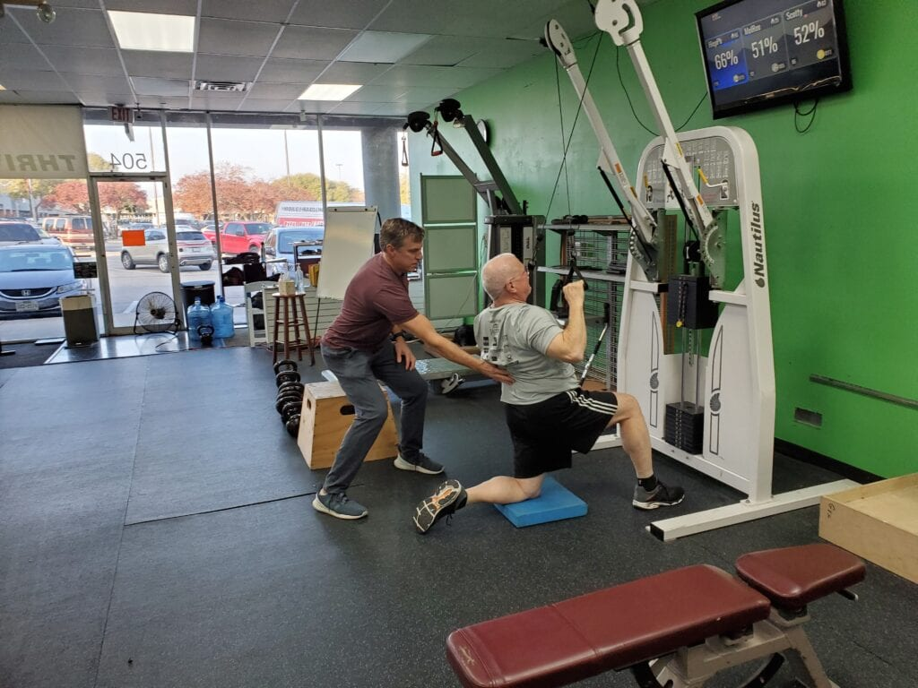 John guiding man in how to use an exercise machine