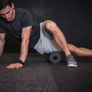 man using a foam roller for mobility warmup