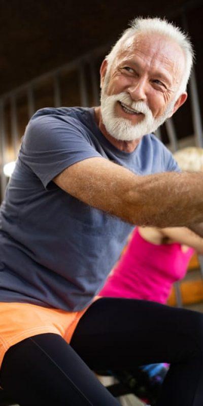 fit older man smiling on exercise bike