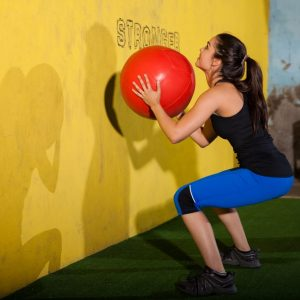 young woman does squat plus wall throw with medicine ball
